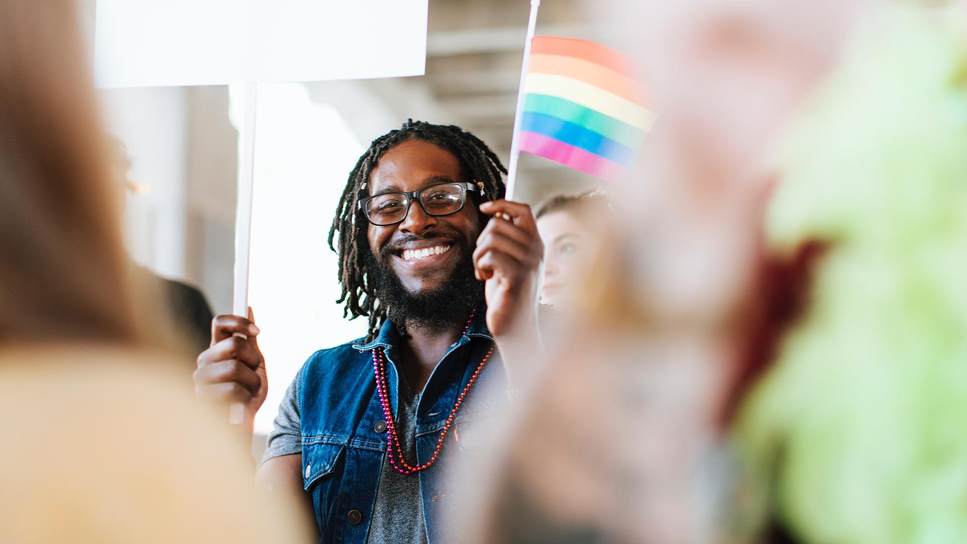 A person holding a rainbow flag