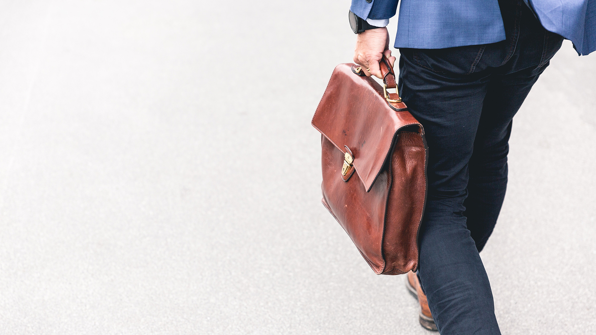 A man walking with a leather briefcase